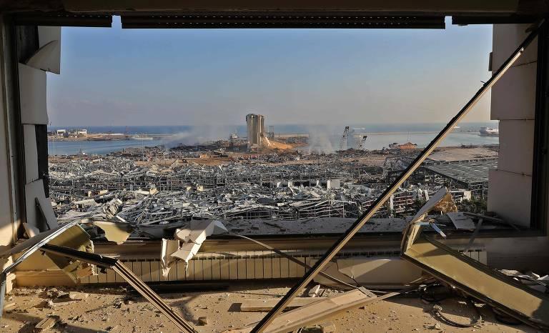 Vista de zona portuária destruída enquadrada por janela estilhaçada
