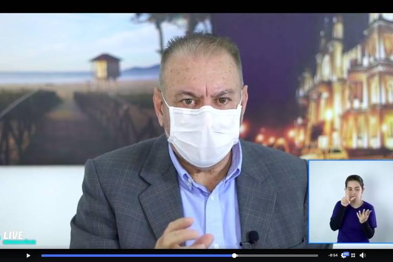 O prefeito de Itajaí (SC), Volnei Morastoni (MDB), de máscara, fala em vídeo sobre tratamentos contra a Covid-19; no canto direito, mulher faz leitura em libras