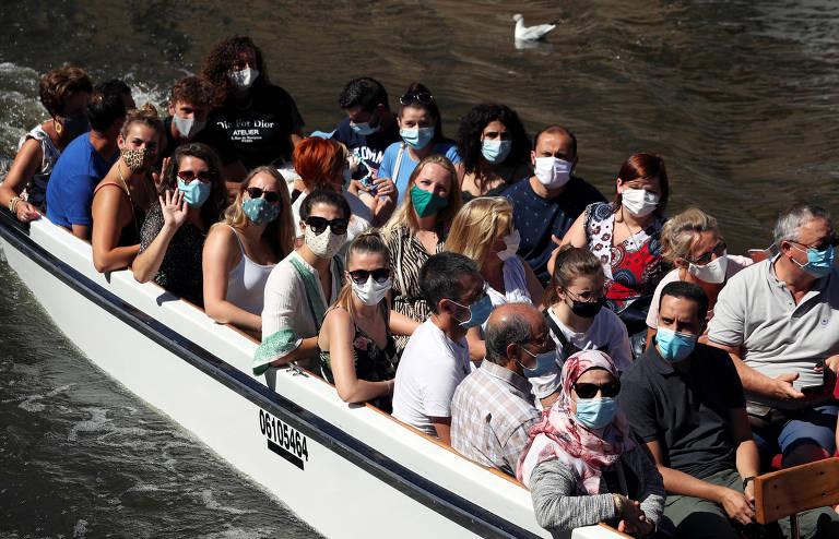 Pessoas usam máscaras enquanto fazem um passeio de barco em um canal no centro de Bruges, na Bélgica