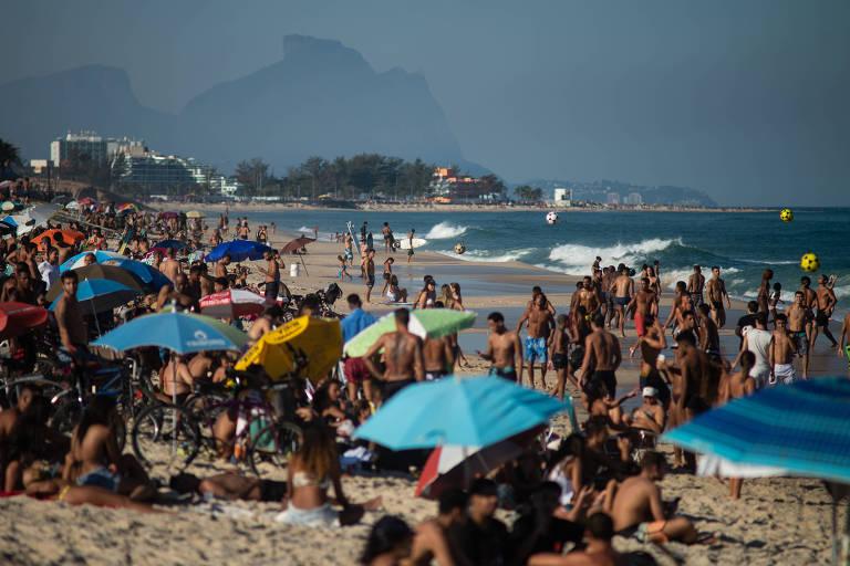 Guardas-sóis e multidão na areia da praia da Macumba, no Rio de Janeiro