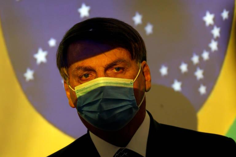O presidente Jair Bolsonaro participa em Brasília de cerimônia do programa Mais Luz para a Amazônia, do Ministério de Minas e Energia; ele usa uma máscara de proteção nas cores verde e amarelo