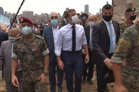 A pool video grab shows French President Emmmanuel Macron (C) inspecting the damages at the port of Lebanon's capital Beirut, on August 6, 2020, where a massive explosion killed more than 100 people and devastated the city. (Photo by - / POOL / AFP)