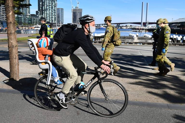 Ciclista passa por soldados e policiais; ao fundo, rio
