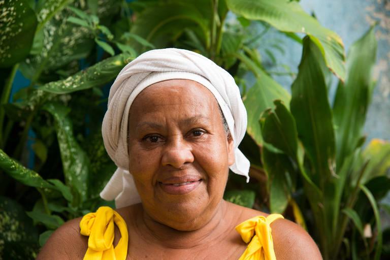 Suzana Sapucaia Dias, 63, sorri vestida de turbante branco e blusa amarela