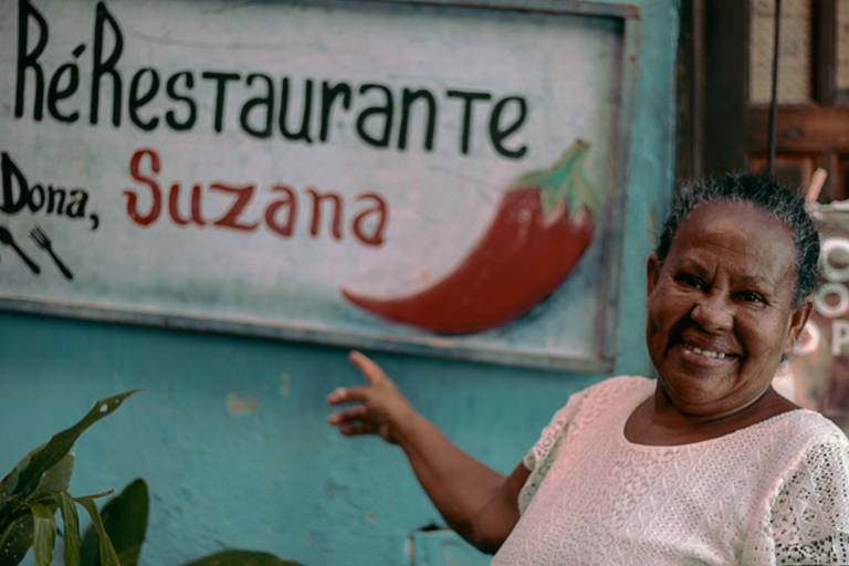 Dona Suzana, 63, aponta para o seu estabelecimento, o RéRestaruante , em Salvador