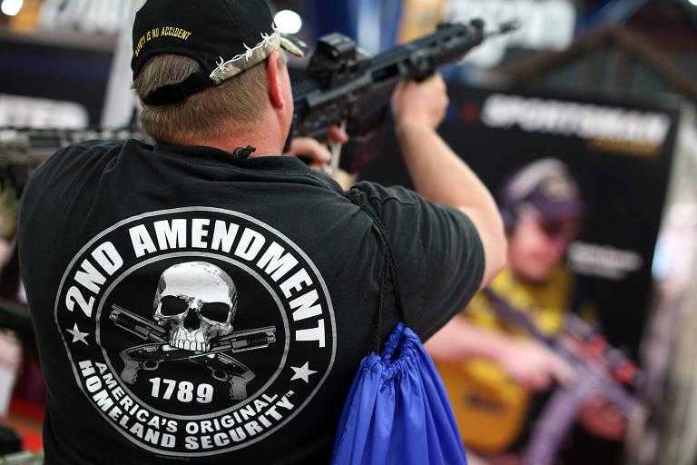 Homem com camiseta em defesa da segunda emenda da Constituição americana testa rifle durante encontro da NRA, em Houston, no Texas