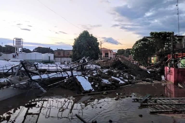 Madeira, pedaços de cimento e outros destroços estão espalhados no chão, com uma árvore em pé ao fundo, no entardecer do dia.
