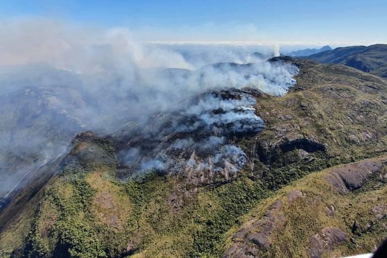 Imagem aérea mostra fumaça de um incêndio no alto de uma montanha