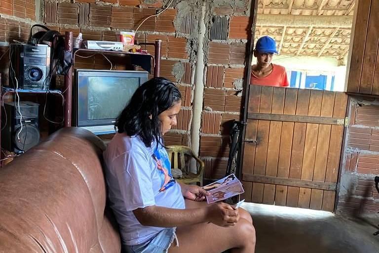 Um mulher está sentada no sofá vendo fotos em uma casa sem reboco; ao fundo, um homem a observa da porta