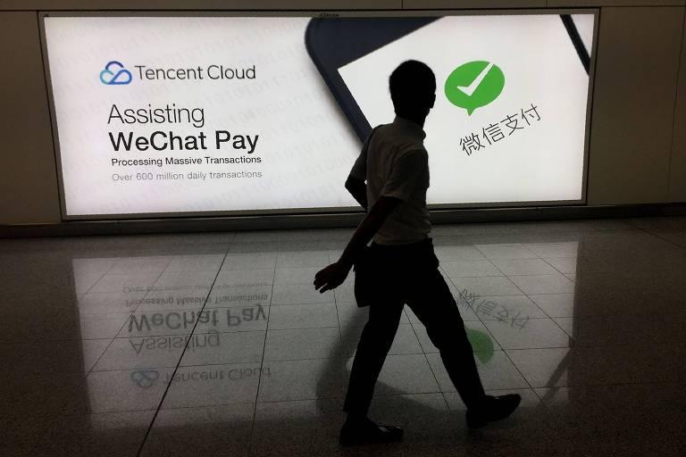 Placar luminoso mostra logo do WeChat enquanto pessoa caminha em frente