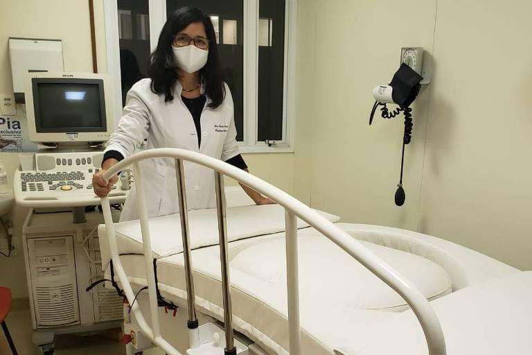 Fisioterapeuta Claudia Oliveira com a cama e colchão que protegem a barriga de grávidas com Covid-19