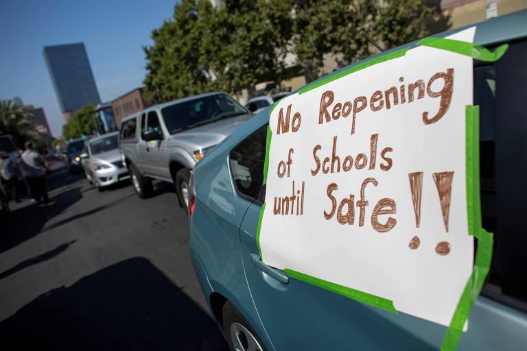 Protesto contra a abertura das escolas em Los Angeles, nos EUA; placa diz 'sem abertura das escolas até que seja seguro'