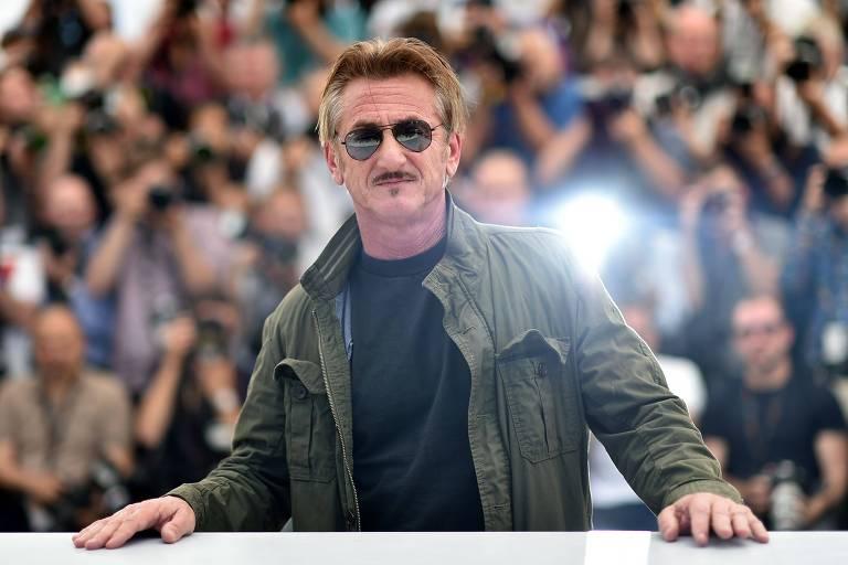 Sean Penn com as mãos apoiadas em superfície branca com público atrás