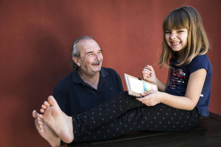 Percival Caropreso, 69, ao lado da filha Laura, 7, no quintal de sua casa em Cotia (SP)