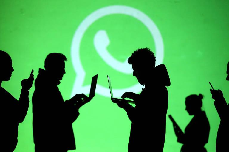 Silhuetas pretas usando celulares e notebooks param na frente de uma tela onde o logo do WhatsApp está projetado em verde