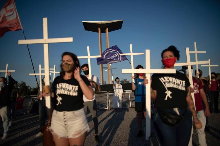 Manifestantes, usando máscaras, seguram cruzes brancas