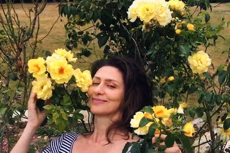 Maria Fernanda Cândido ao redor de flores amarelas