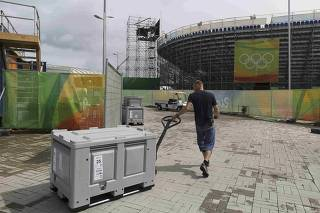 A woker pulls a storage bin in the Olympic Park in Rio de Janeiro