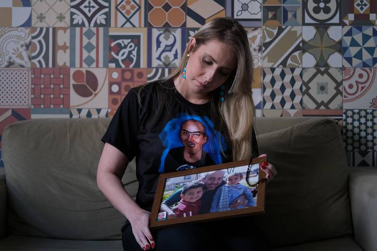 Anna  Magdalena segurando foto com imagem do marido, que morreu há cerca de um mês de Covid-19