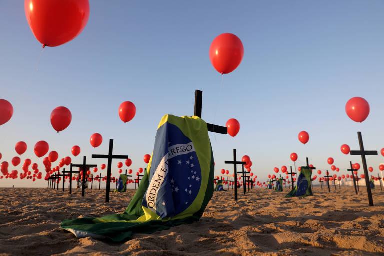 bandeira do brasil estendida entre cruzes e balões vermelhos nas areias da praia