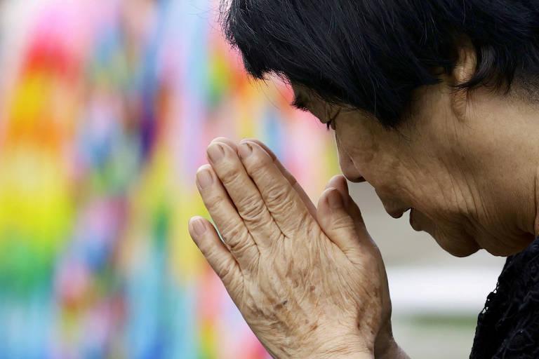 Com as mãos juntas e próximas ao rosto, mulher ora pelas vítimas do bombardeio de 1945 nos 75 anos da explosão da bomba atômica, em Nagasaki, Japão