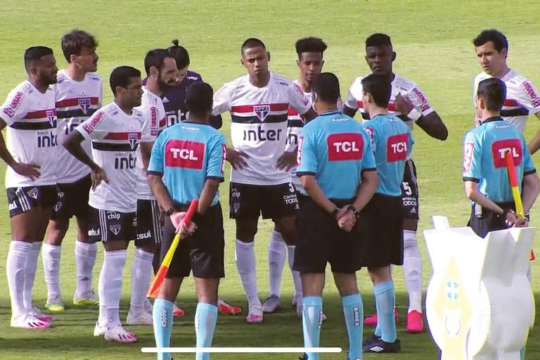 Jogadores do São Paulo conversam com a equipe de arbitragem antes do adiamento da partida