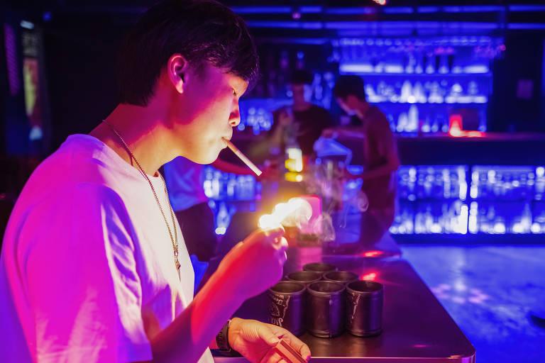 Dono de boate acende cigarro do bairro de Baiyun