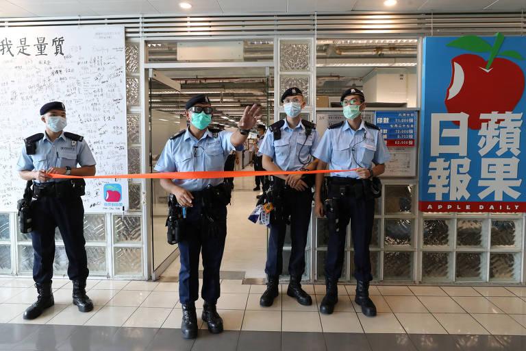 Policiais montam guarda frente a acesso ao prédio de jornal