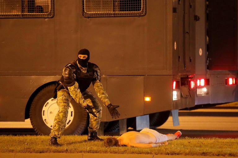 manifestante caído de bruços no chão em frente a furgões da polícia; policial gesticula como a pedir ajuda, apontando para ele