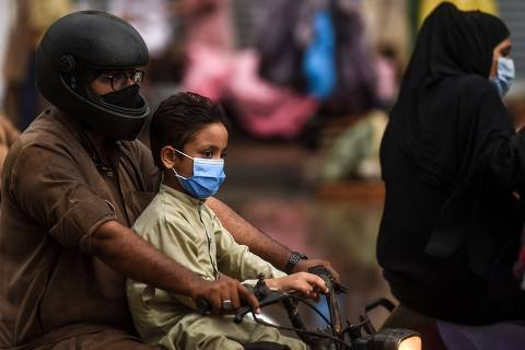 Motorcyclists wearing facemasks as a preventive measure against the COVID-19 coronavirus make their way on a street in the Pakistan's port city of Karachi on August 6, 2020. - Pakistan on August 6 announced it would be lifting most of the country's remaining coronavirus restrictions after seeing new cases drop for several weeks. (Photo by Asif HASSAN / AFP)