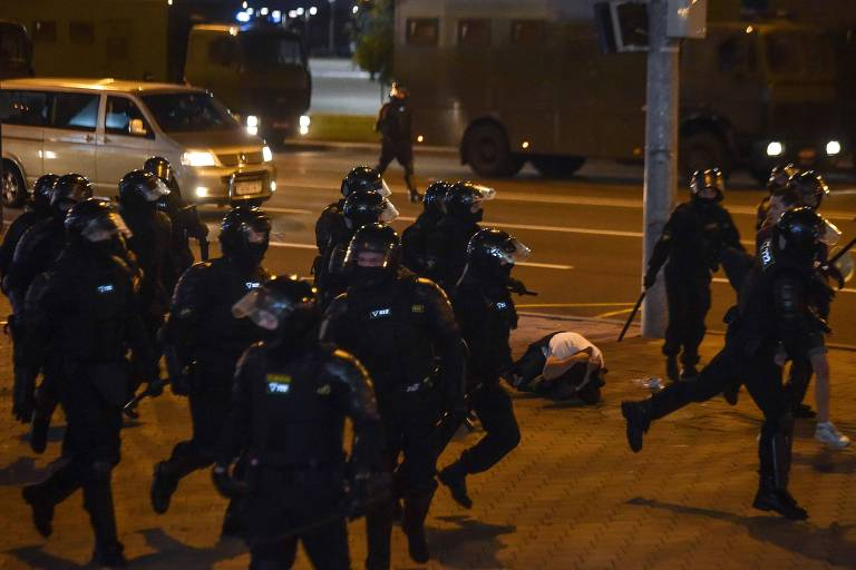 Policiais passam por manifestante durante repressão a ato contra Lukachenko em Minsk