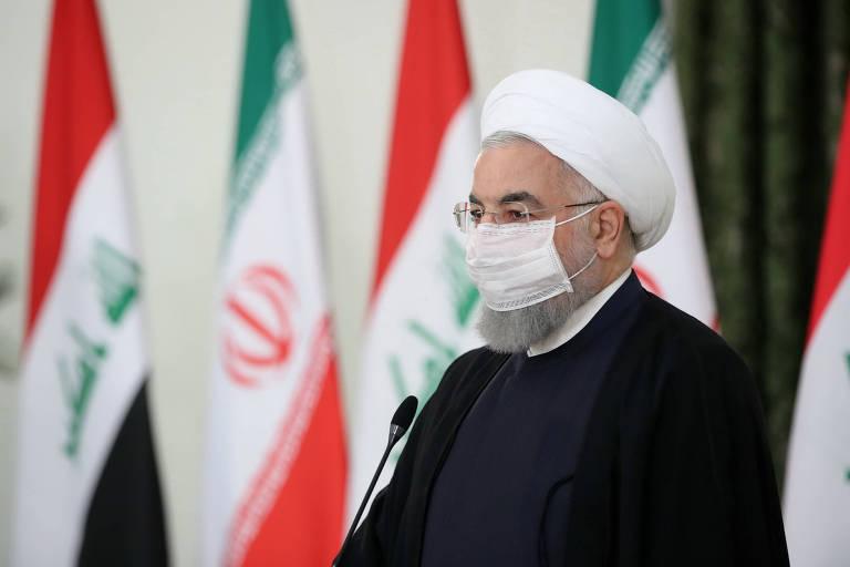 Presidente do Irã fala ao microfone usando máscara