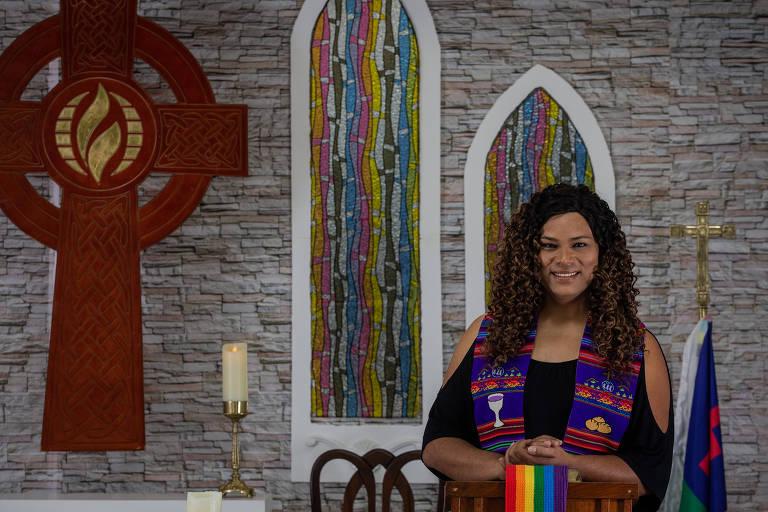 No altar de uma igreja, com um crucifixo, vela e vitrais coloridos, uma mulher com uma estola azul desenhada, com as mãos sobre uma candeira com as cores lgbt