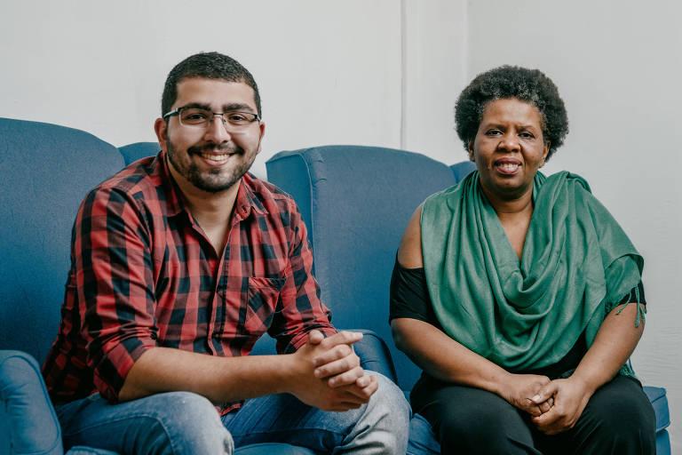 Sorrindo e sentados num sofá azul, um rapaz branco de óculos e camisa xadrez ao lado de uma mulher negra que veste uma blusa preta coberta por um lenço verde