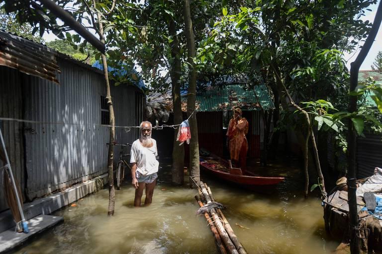 Moradores posam frente a suas casas em área alagada