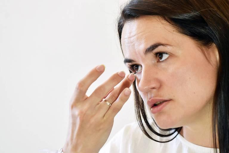 a candidata, de roupa branca e cabelos escuros lisos soltos,  passa o dedo sob olho. na sua mão ha uma aliança