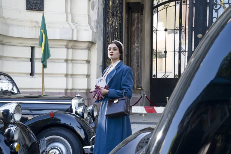 """Aracy de Carvalho (Sophie Charlotte) em frente ao Consulado Brasileiro em cena de """"O Ano de Hamburgo"""". Mulher com roupas antigas, da década de 1930, parada ao lado de um carro"""