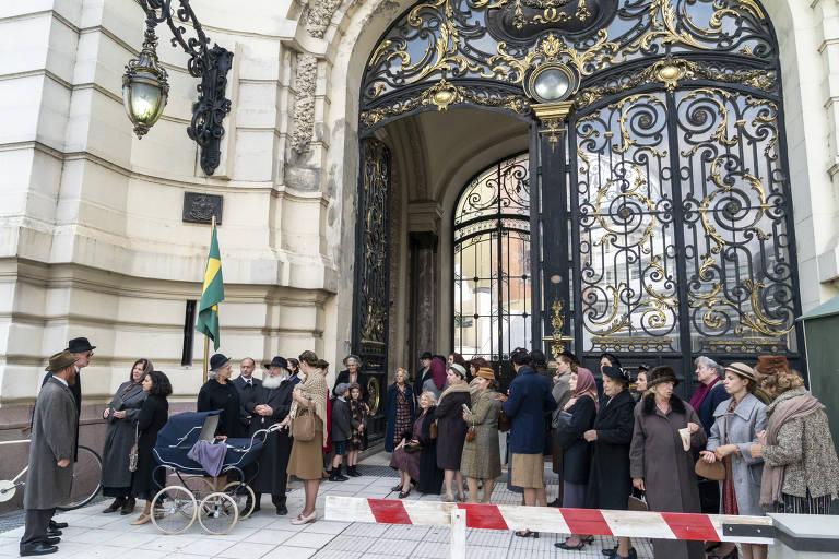 """Fila de famílias judiais em frente ao Consulado Brasileiro em cena da série """"O Anjo de Hamburgo"""""""