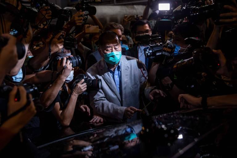 De máscara contra covid, Jimmy Lai entra em carro cercado por câmeras e jornalistas.