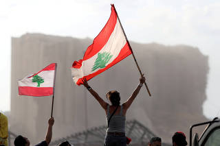Demonstrators wave Lebanese flags during protests near the site of a blast at Beirut's port area