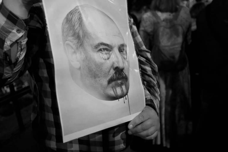 Manifestante com cartaz anti-Lukachenko na embaixada bielorrussa em Moscou