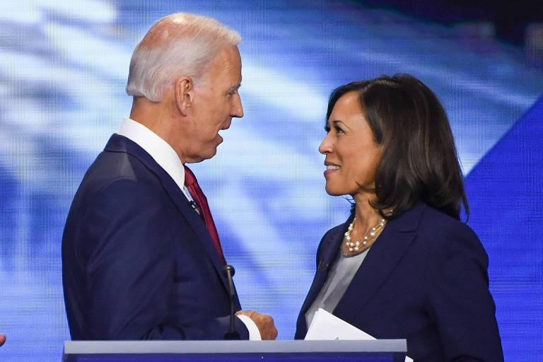 Joe Biden conversa com Kamala Harris em um palco de debate