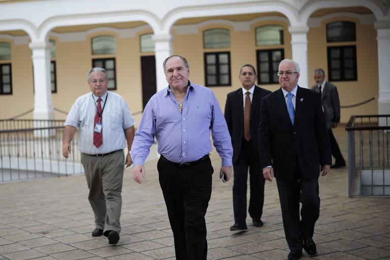 Abdalá Bucaram, vestido de camisa social e com um cordão de ouro no pescoço, caminha com outros três homens de terno
