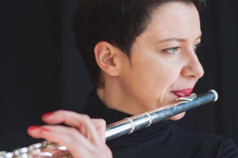 Moça de cabelo escuro bem curto toca flauta transversal