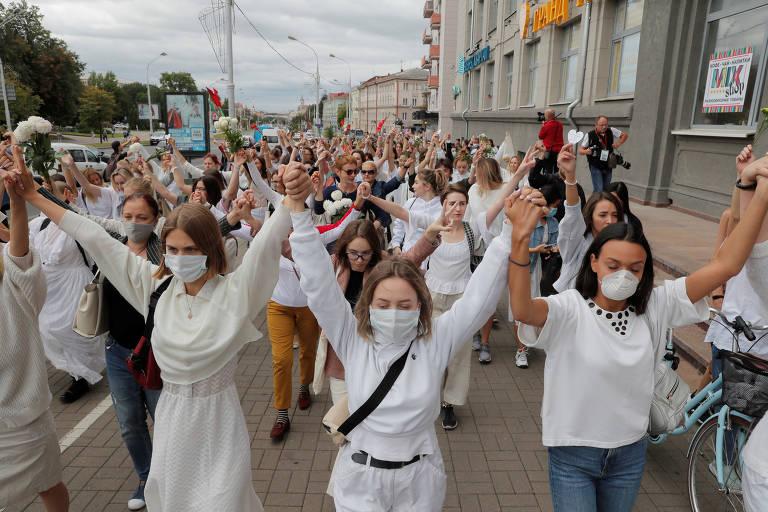 De máscara e roupas brancas, mulheres caminham em Belarus com mãos dadas e braços erguidos