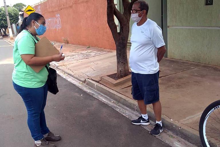 mulher com prancheta na mão e máscara conversa na rua com homem de máscara e bermuda