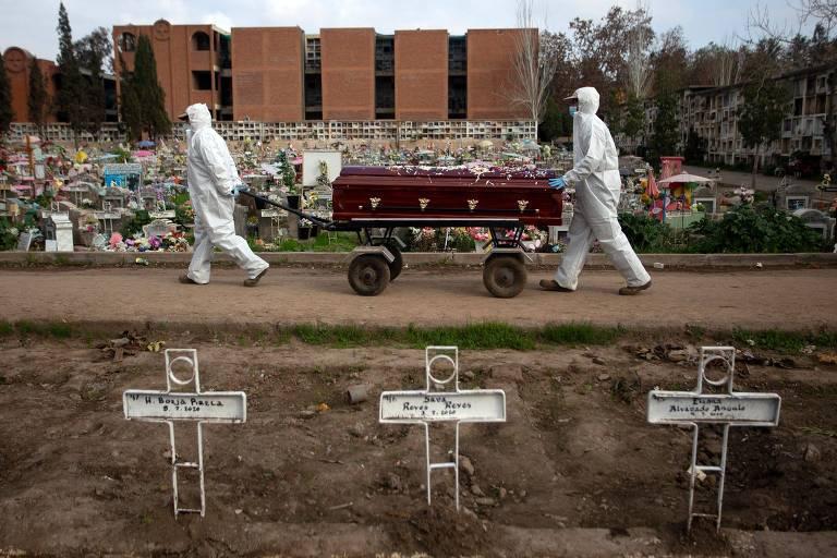 Funcionários carregam caixão em cemitério em Santiago, capital do Chile, durante a pandemia de coronavírus