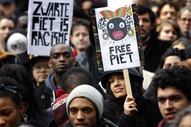 """Em Amsterdã, manifestantes protestam com cartazes com as frases """"Zwarte Piet é racista"""" e """"liberte Piet"""", em referência ao personagem de festas folcóricas na Holanda"""