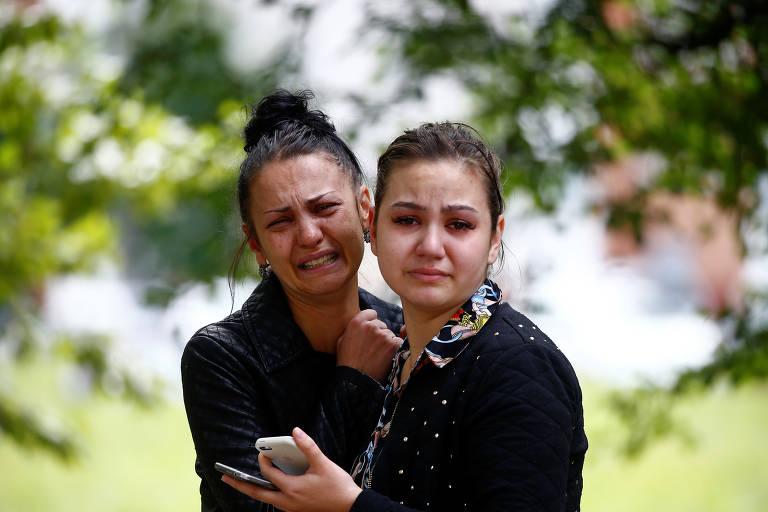 Duas garotas de roupa preta e cabelo preso choram