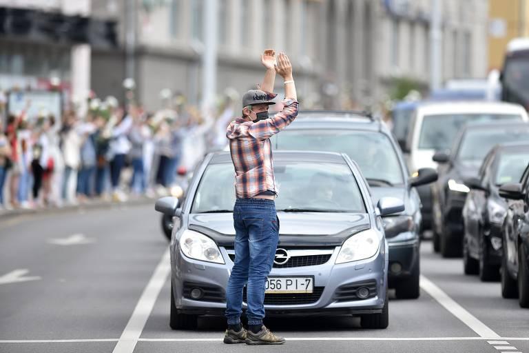 Homem aplaude em frente a carros enquanto mulheres com flores protestam na calçada